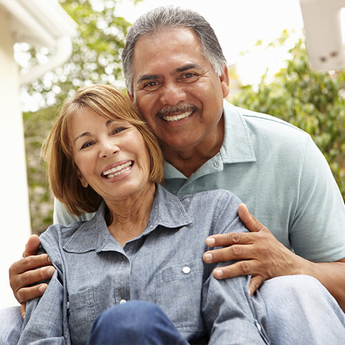 A mature couple with big smiles to show that your dentists in Salinas, CA offer dental implants.