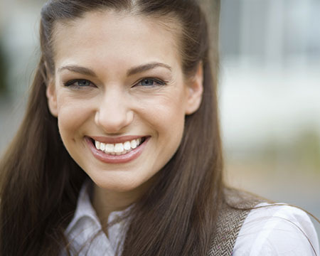 A smiling woman with perfect teeth, thanks to dental bonding
