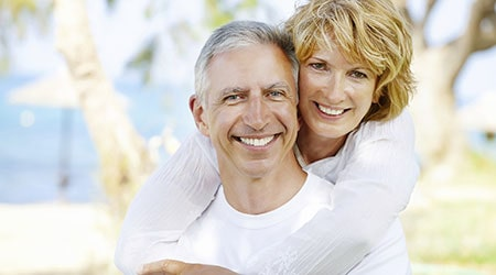 Older couple with beautiful teeth because of natural-looking dentures