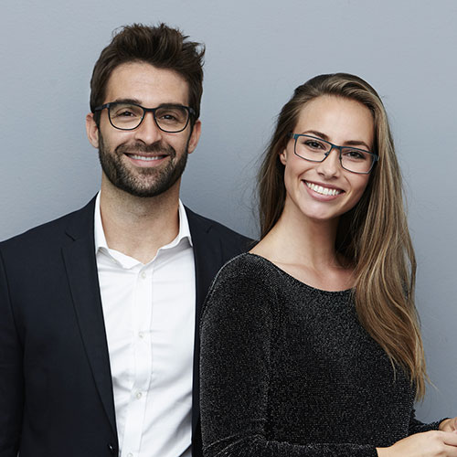A young professionals couple with glasses and straight white teeth to show that our dentists in Salinas. CA offer cosmetic dentistry.